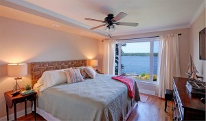 Guest bedroom on main level with king bed and lake views .