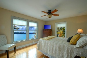 First guest bedroom with beautiful lake views and queen bed on second level.