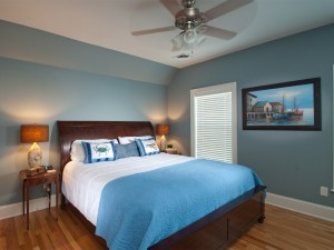 Coastal themed guest bedroom with king size bed .