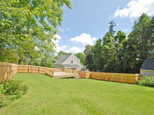 Expansive backyard with spacious deck and privacy fencing .