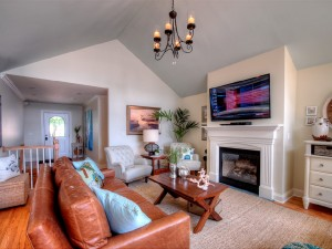 Main level living room with a gas fireplace and 60 inch television.