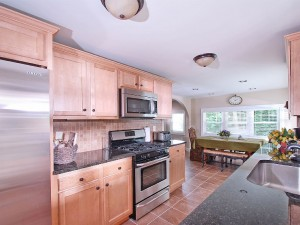 Kitchen with maple cabinets and granite counters .