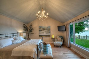 Enjoy the lake view from the main floor master bedroom with king bed .