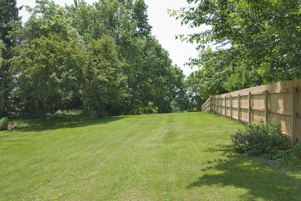 Expansive backyard with spacious deck and privacy fencing