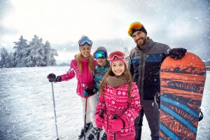 Smiling family enjoying winter sports and vacation on snow in mountains in Finger Lakes